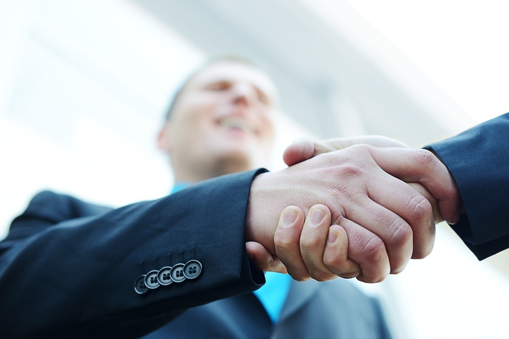 Business shaking hands in front of modern building with copy space (selective focus).jpeg